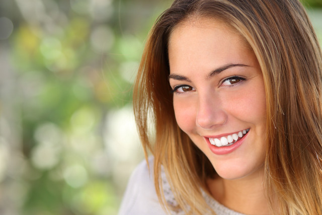 Beautiful-woman-with-a-whiten-perfect-smile-outdoor-with-a-green-background