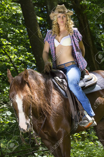Sexy-blonde-cowgirl-riding-on-her-horse-in-the-woods.jpg