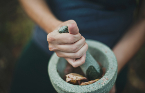 An image of a woman using an pestle and mortar