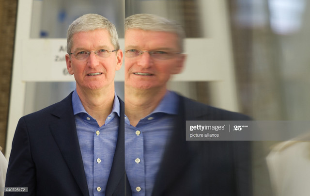 Tim-Cook-CEO-of-Apple-Inc-is-mirrored-in-a-sheet-of-glass-during-a-factory-visit-at-Seele-glass-manu.jpg