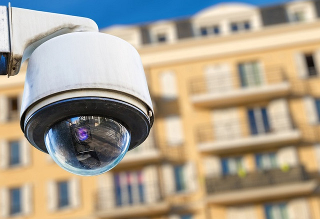 security-CCTV-camera-or-surveillance-system-with-modern-luxury-residence-on-blurry-background