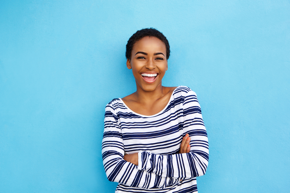 woman wearing a striped shirt smiles in front of a blue background