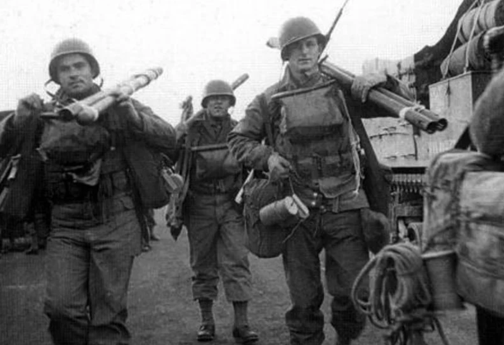 American soldiers after the Normandy landings. They carry Bangalore torpedoes in their hands.