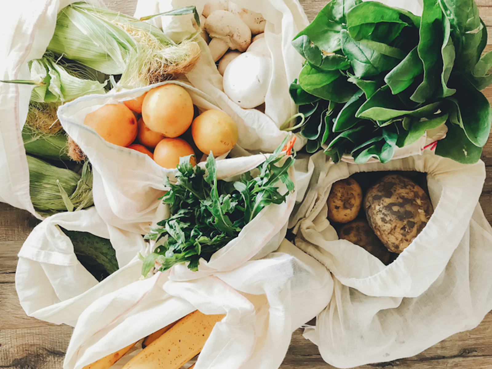 fresh-vegetables-in-eco-cotton-bags-on-table-in-the-kitchen-lettuce-corn-potatoes-apricots-bananas-r