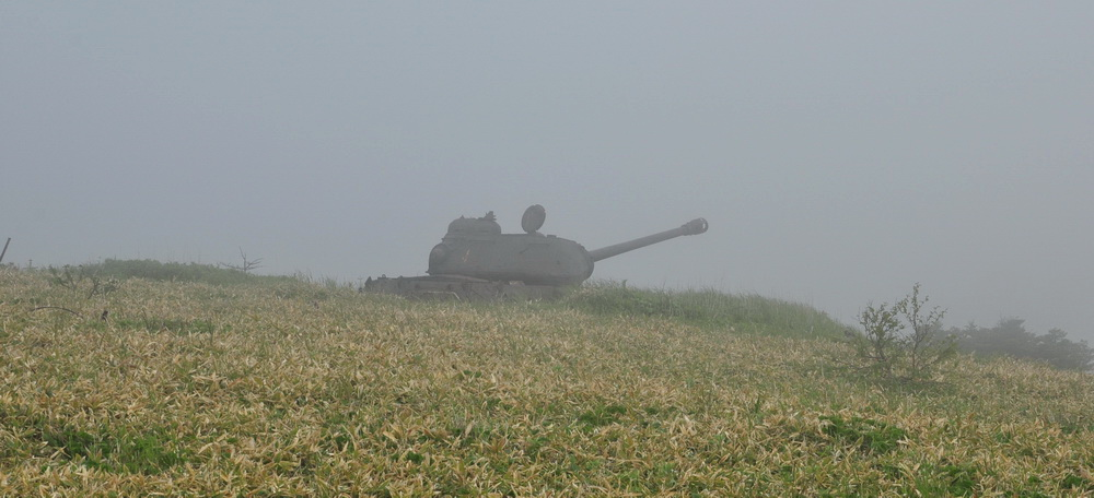 The silhouette of an abandoned IS-2 tank can be seen in the fog.