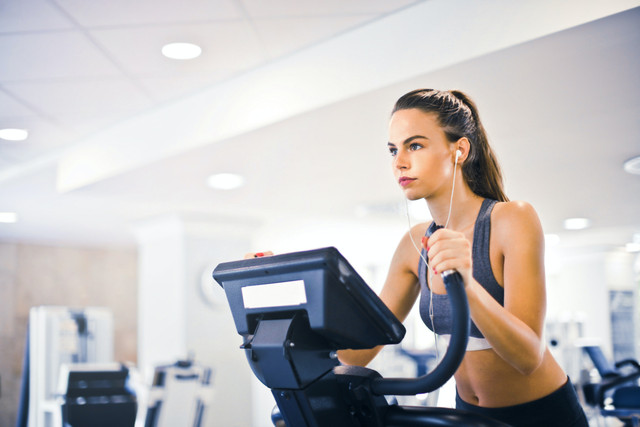 young-female-athlete-training-alone-on-treadmill-in-modern-3768916