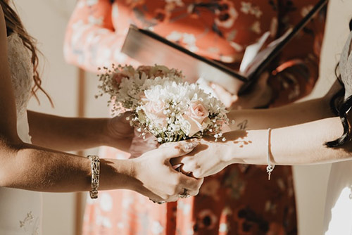 An image of two brides holding a bouquet each.