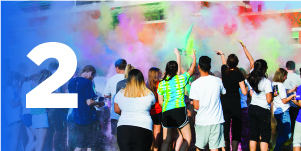 #2: A group of students throwing colorful powder into the air as a part of Holi Festival on campus