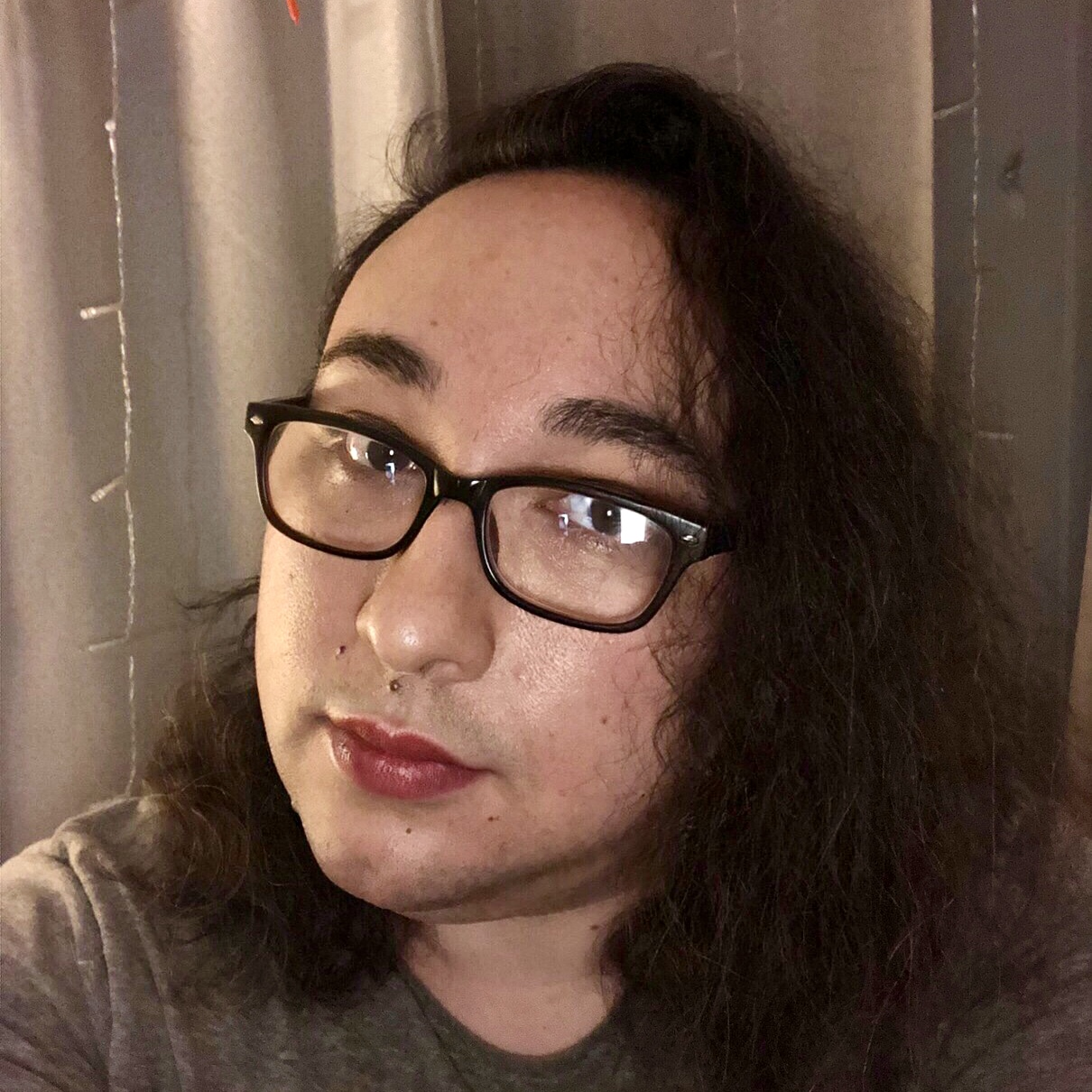 A selfie of Doryen Chin, a mixed-race Asian-American woman taken indoors at night. She has shoulder length dark hair, parted on the side, dark rectangular glasses, and wears dark red lipstick, and gazes at the viewer with a slight smile.