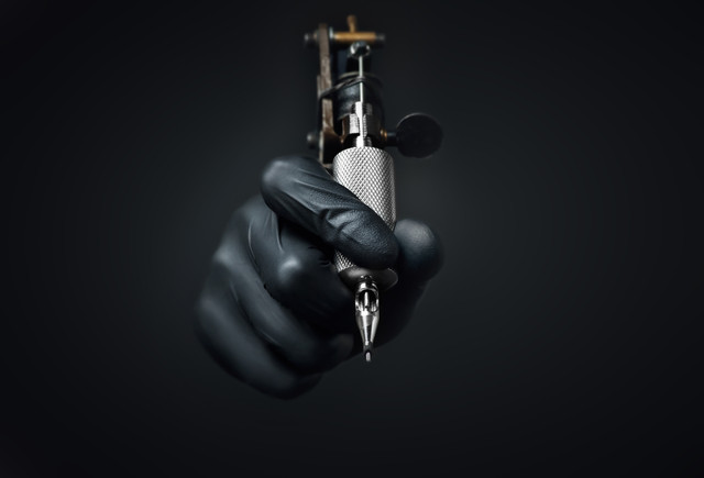 Tattoo-artist-holding-tattoo-machine-on-dark-background-Machine-for-a-tattoo-concept