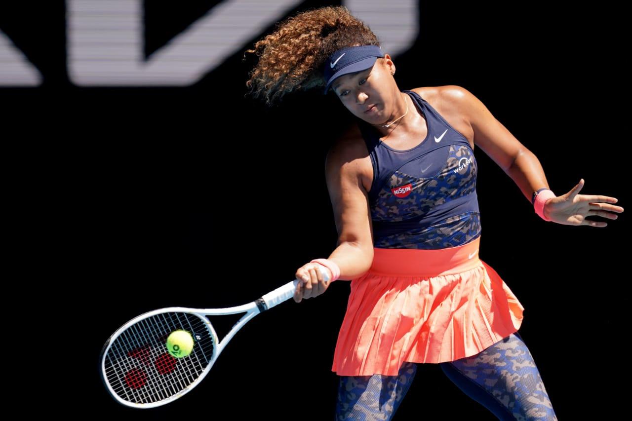 Naomi Osaka rebate a bola segurando uma raquete com a mão direita.