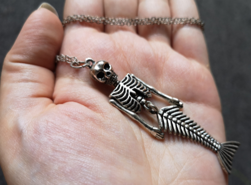 An image of a mermaid skeleton necklace.