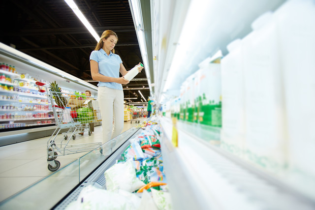 Young-female-choosing-dairy-products-in-supermarket