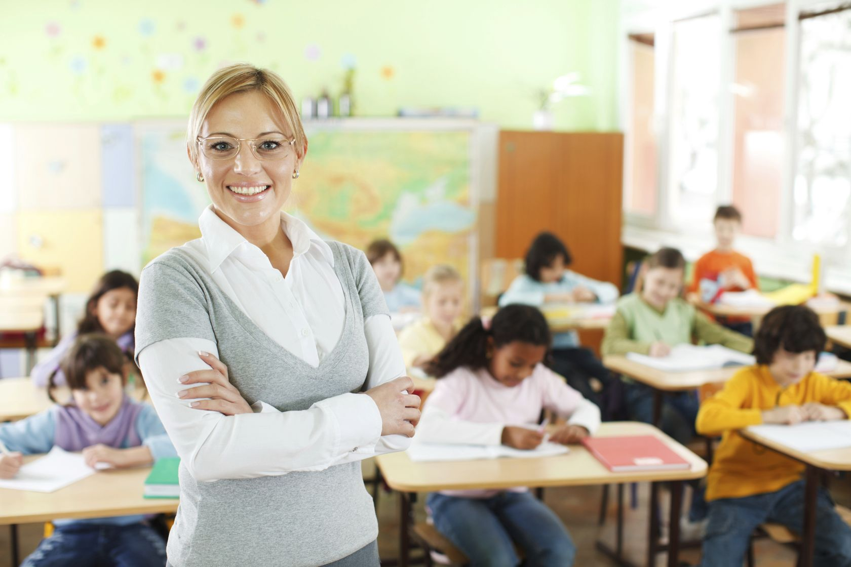 Beautiful-smiling-female-teacher-standing-and-looking-at-the-camera-In-the-background-there-is-a-gro