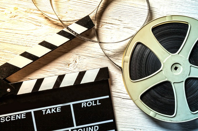 Film-camera-chalkboard-and-roll-on-wooden-table