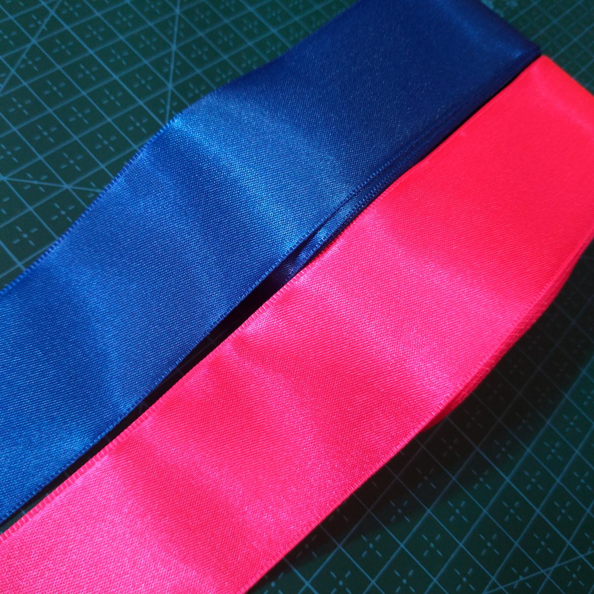 Imagem mostra os detalhes de duas fitas, uma azul e uma rosa.