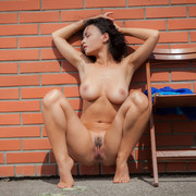 pammie-lee-poses-naked-by-the-wall-showing-off-her-knockers-11