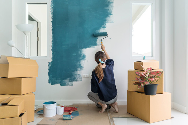 Young-asian-happy-woman-painting-interior-wall-with-paint-roller-in-new-house