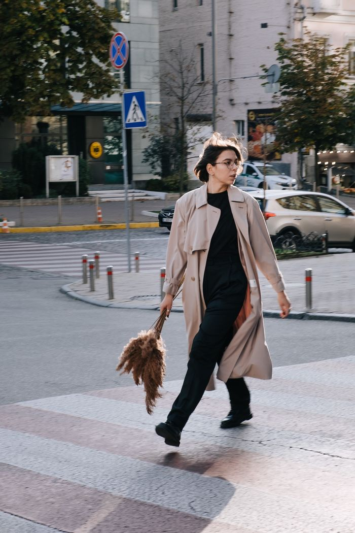 A woman in motion walking on a crosswalk while looking the wrong way. Her feet are carrying her in one direction but her head is tilted to look in another.
