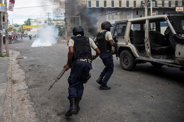 epa07365789-Police-take-cover-during-a-protest-in-Port-au-Prince-Haiti-12-February-2019-Haitians-con