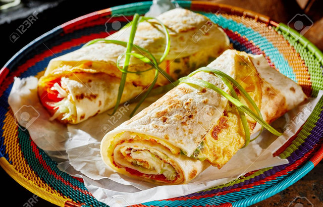 Ugandan-Rolex-Rolls-street-food-on-a-brightly-colored-basket-with-egg-omelette-and-vegetables-rolled