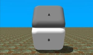 Dark gray cube on top of white cube with the sides having identical colors due to lighting but perceived differently by the eyes due to visual illusion