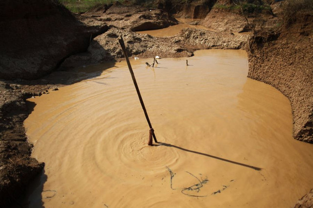 A-man-holds-a-stick-as-he-installs-a-pump-to-extract-mud-at-a-primitive-gold-mine-in-Panompa-near-Ph