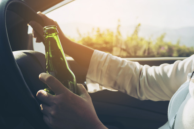 Woman-holding-beer-bottle-while-driving-a-car