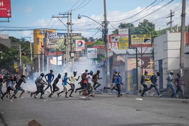 epa07365792-People-run-down-a-street-during-a-protest-in-Port-au-Prince-Haiti-12-February-2019-Haiti