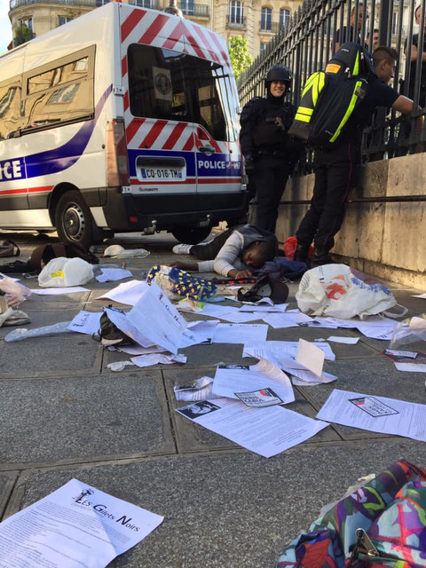 Police-officer-smiles-as-man-lies-injured-on-the-ground-leaflets-strewn-around