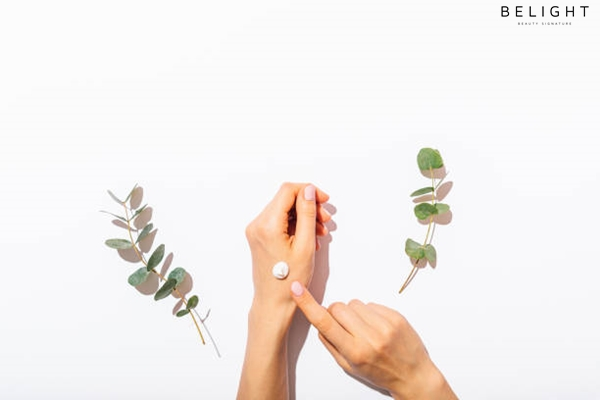 Woman-s-hands-apply-cosmetic-cream-next-to-eucalyptus-branches-on-white-table-flat-lay-arrangement