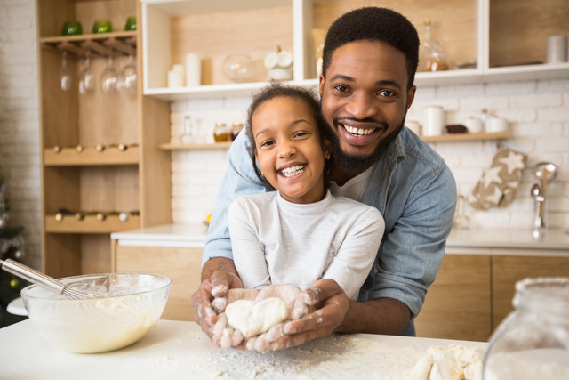 Love-concept-Afro-dad-holding-his-daughter-hands-with-heart-shaped-pastry-inside-kitchen-interior-co