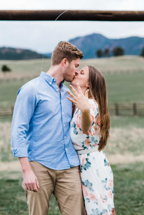 Newly engaged couple kiss while future bride shows off ring