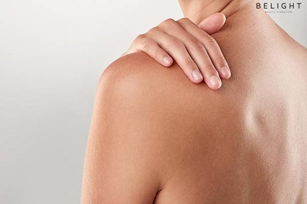Closeup-studio-shot-of-a-woman-touching-her-bare-shoulder