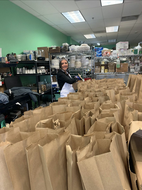 Caterer at A Spice of Life prepares bags of food to be donated