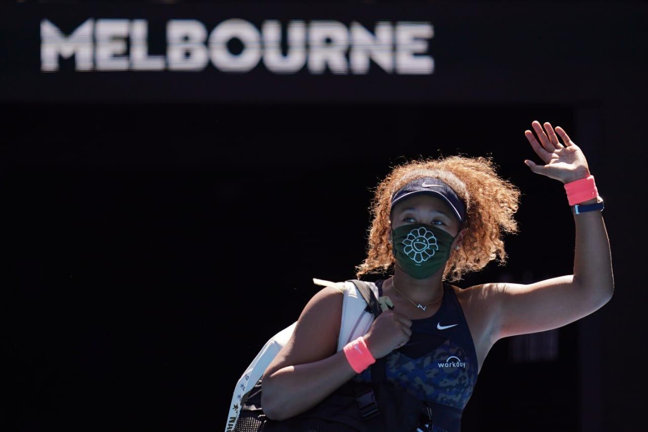 De máscara, Osaka acena para o público do Australian Open