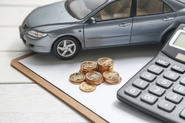 car-model-calculator-and-coins-on-white-table