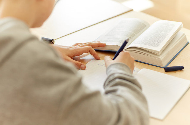education-learning-and-people-concept-close-up-of-student-boy-with-notebook-and-book-writing-school