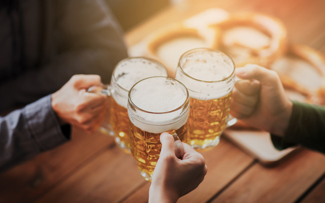 people-leisure-and-drinks-concept-close-up-of-hands-clinking-beer-mugs-at-bar-or-pub