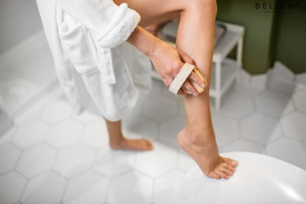 Woman-scrubbing-her-legs-with-a-brush-making-skin-peeling-in-the-bathroom