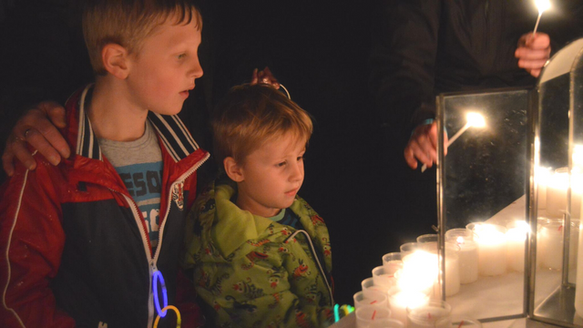 Photo of 2 bereaved siblings lighting candles in memory, young children