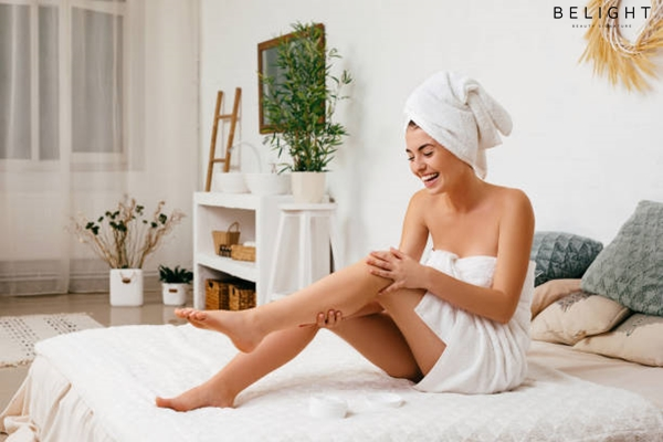 Young-beautiful-woman-in-towel-applying-cream-on-her-legs-after-shower-at-home