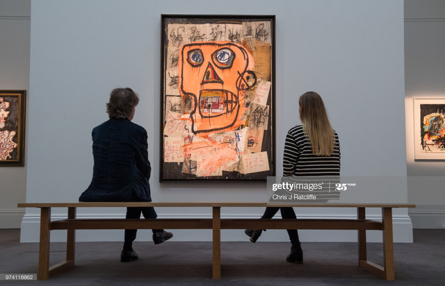 LONDON-ENGLAND-JUNE-14-A-man-and-woman-sit-on-a-bench-in-front-of-Untitled-by-Jean-Michel-Basquiat-e.jpg