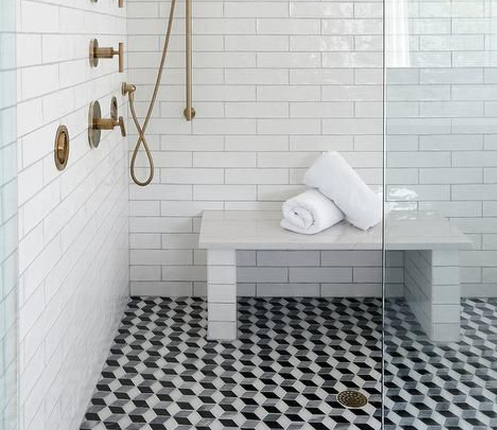 A seamless glass shower door opens to black and white geometric floor tiles fixed beneath a subway tiled bench with a white quartz top.