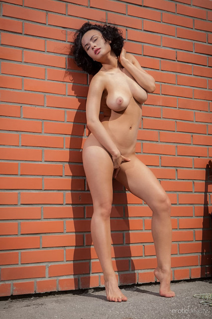 pammie-lee-poses-naked-by-the-wall-showing-off-her-knockers-09