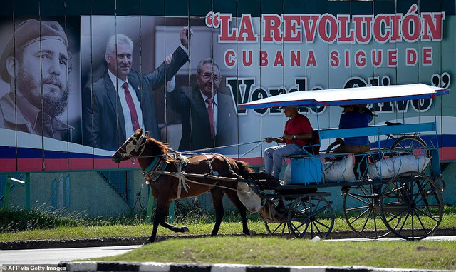 22160934-7785767-A-man-rides-a-horse-carriage-in-front-of-a-billboard-depicting-C-a-40-1576170216505