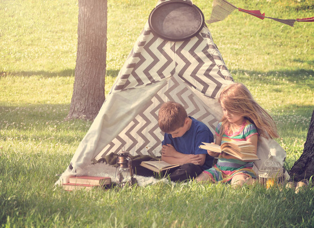 Two-Children-are-sitting-in-a-tent-tipi-reading-books-and-learning-outside-in-the-spring-for-an-educ