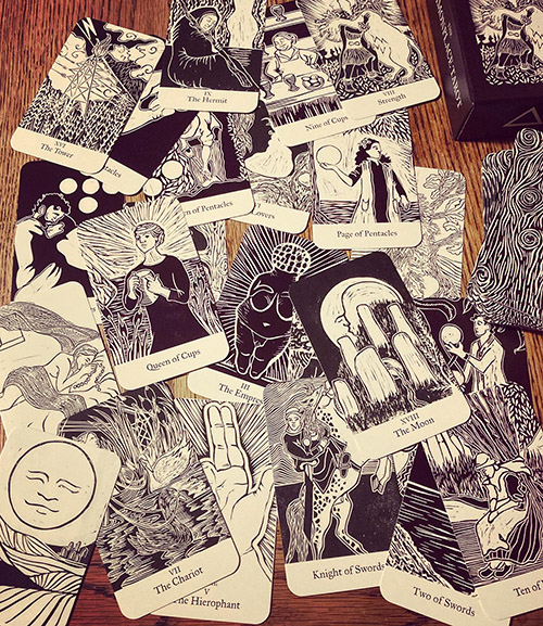An image of some of the cards from the second edition of the Commonplace Tarot deck, scattered across a table.