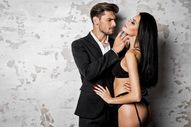man in suit inspects a lady with long dark hair in black lingerie