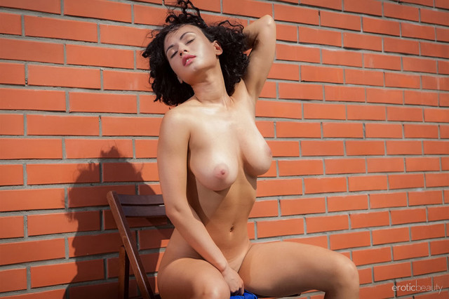 pammie-lee-poses-naked-by-the-wall-showing-off-her-knockers-02